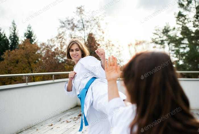 Young women practising karate outdoors on terrace.