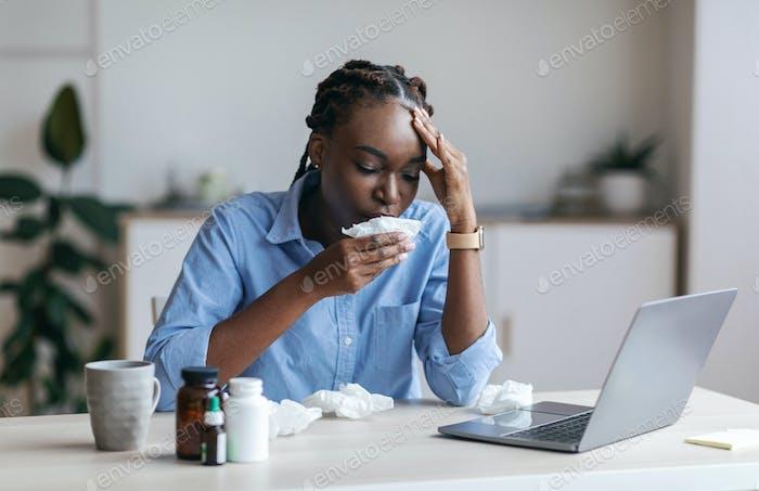 Kranke schwarze Geschäftsfrau leidet an Virus bei der Arbeit, das Gefühl unwohl im Büro