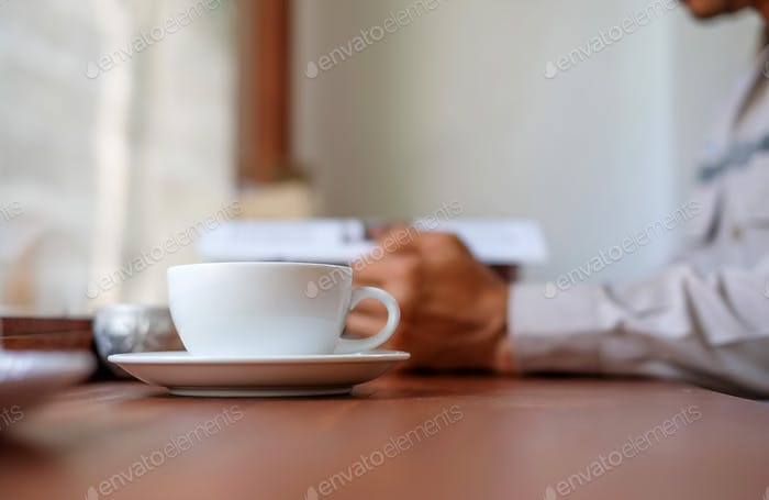Man reading a book with white coffee cup front place.