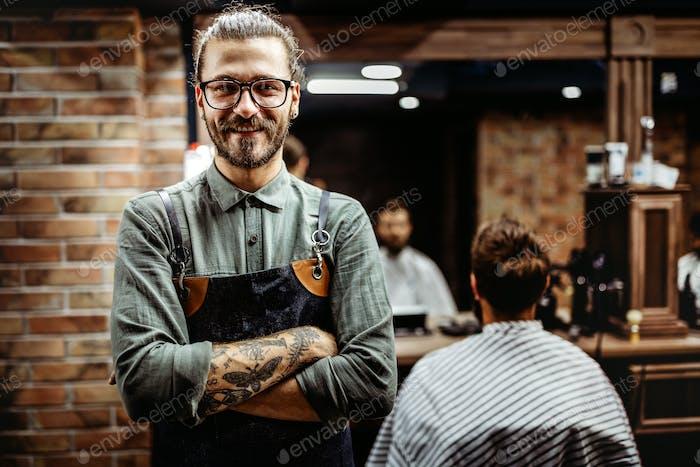 Barbier Mann in einer Schürze mit Armen gekreuzt und glücklich im Salon