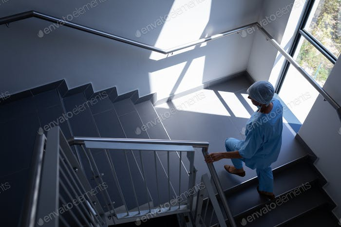High angle view of a Caucasian female surgeon walking up in stairs in hospital