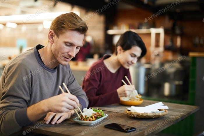 People Enjoying Asian Food in Cafe