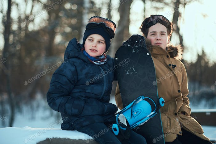 Two brothers are posing for photographer with snowboard