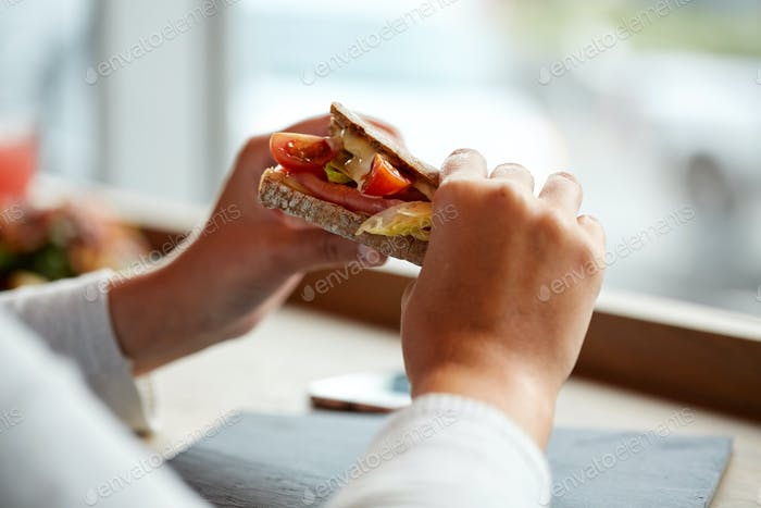 woman eating salmon panini sandwich at restaurant