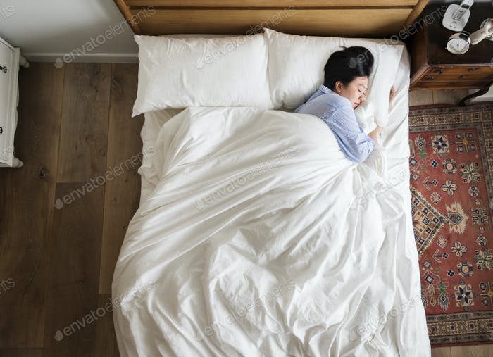 Asian woman on the bed sleeping by herself