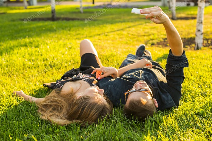 Teenage couple lying on grass and taking selfie on smartphone