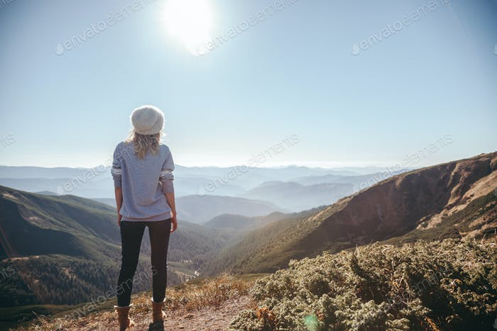 rear view of female traveler looking at mountains on sunny day, Carpathians, Ukraine