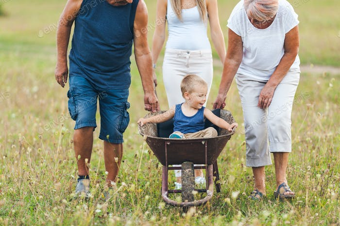 Family pushing their small child in a wheelbarrow
