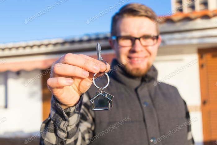Young happy man showing a house key