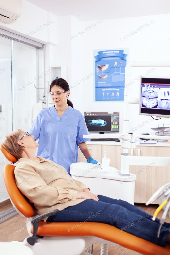Assistant in dental clinic questioning elderly patient