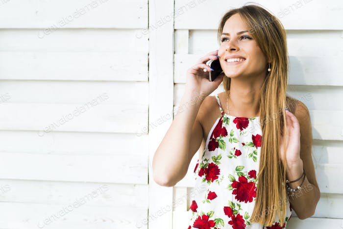 Beautiful young happy woman smiling during a phone call