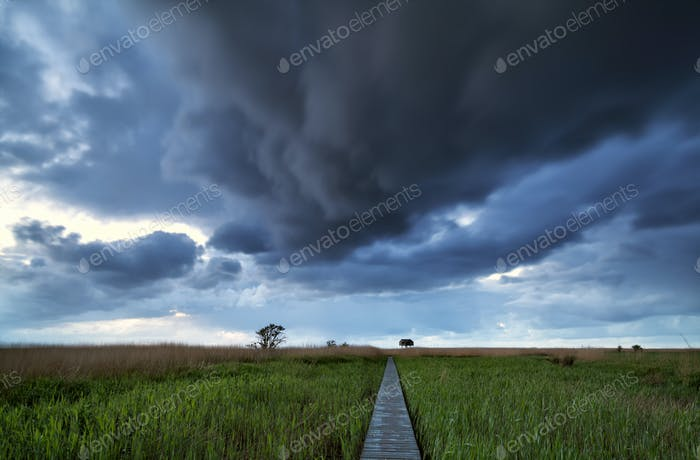 dramatic stormy clouds over pier path