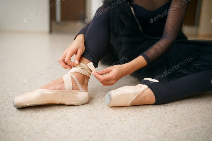 Ballerina sitting on the floor and ties the ribbon