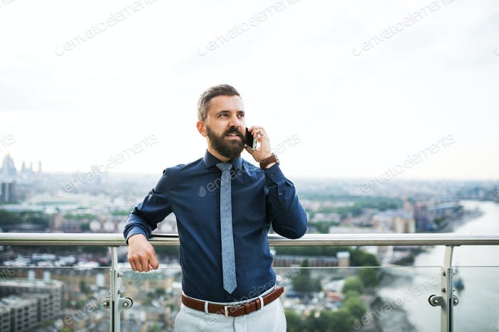 A portrait of businessman with smartphone standing against London view panorama.