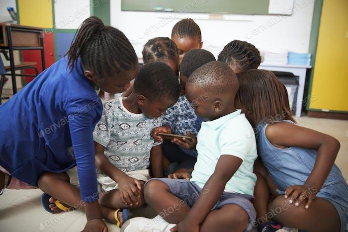 Grundschule Kinder sitzen auf dem Boden Blick auf ein Buch