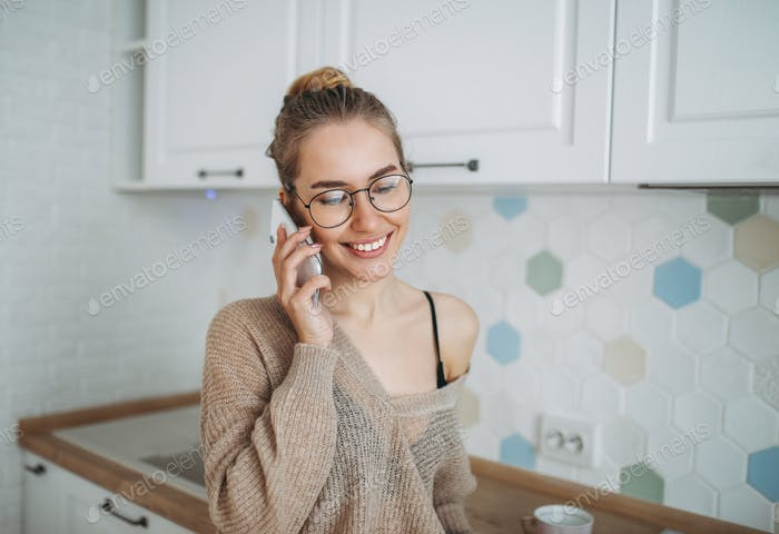 Beautiful smiling girl in cozy knitted sweater using mobile at kitchen
