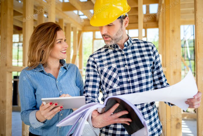 Female homeowner consults blueprints with architect or engineer