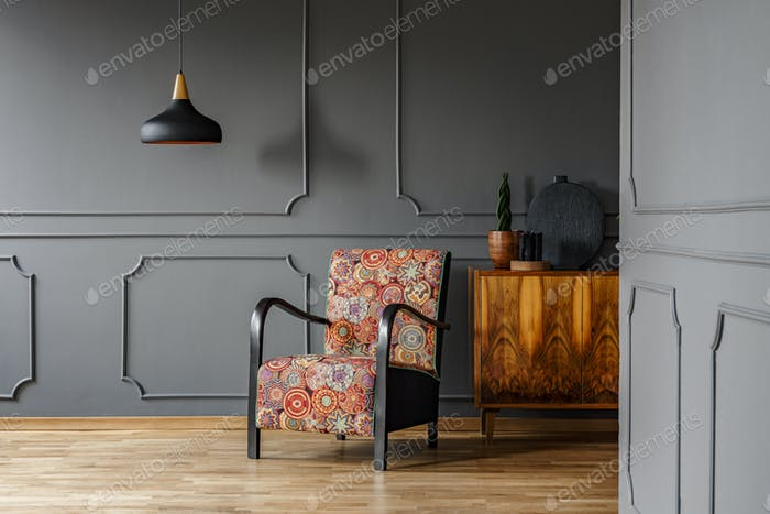 Patterned armchair next to wooden cabinet in grey living room in