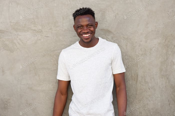 happy young african american man smiling by wall