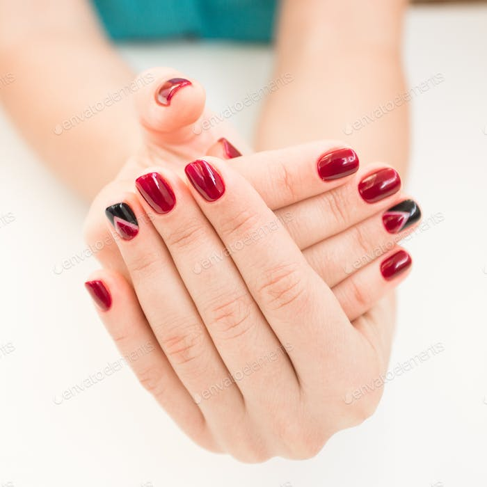Closeup photo of a beautiful female hands with red nails on white background