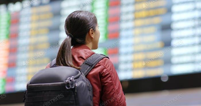 Junge Frau Blick auf die Flugnummer im Flughafen