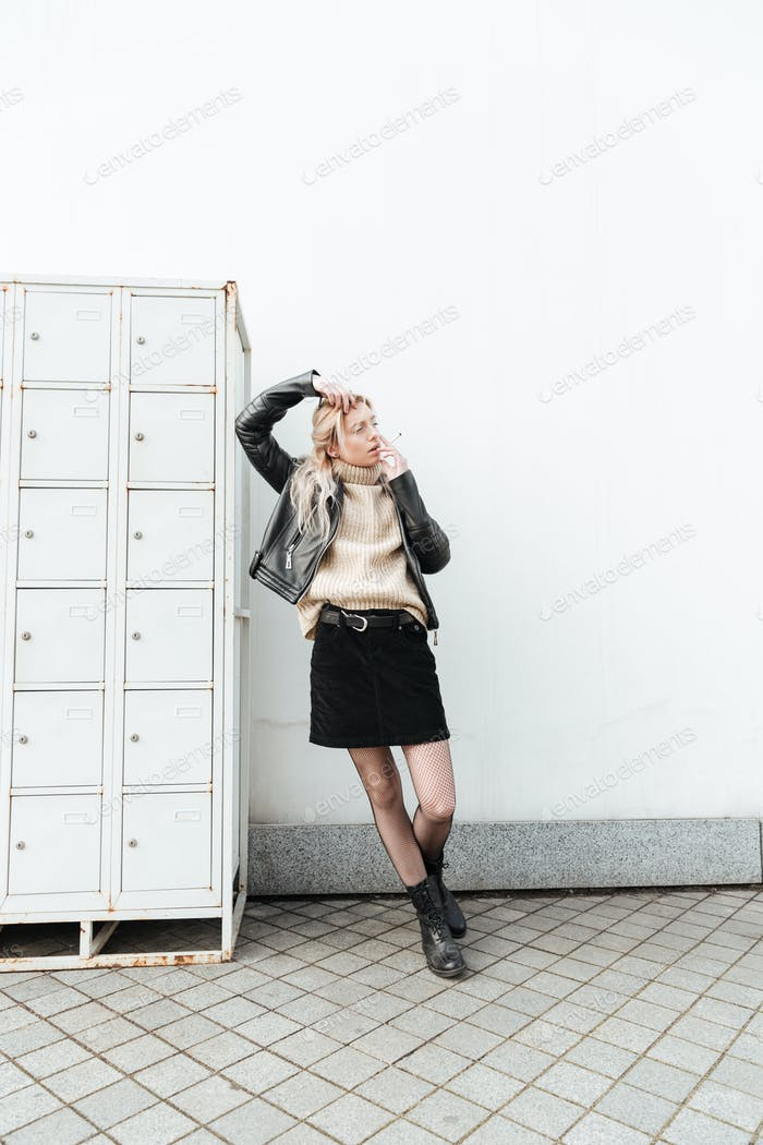 Serious young blonde lady standing near safes.
