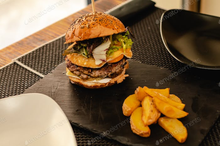 Burger with egg and fries served on restaurant