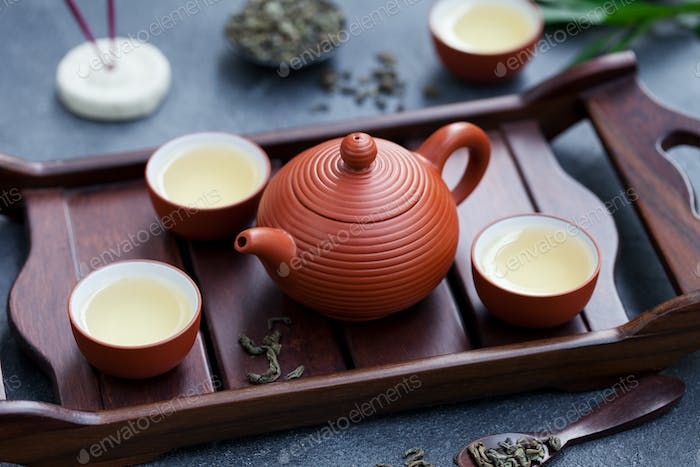 Green Tea in Tea Pot and Bowls, Cups on Wooden Tray. Close up.