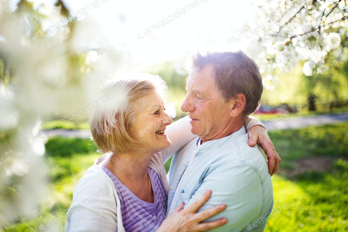 Beautiful senior couple in love outside in spring nature.