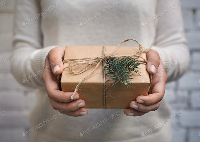 Woman holding craft paper gift box for present