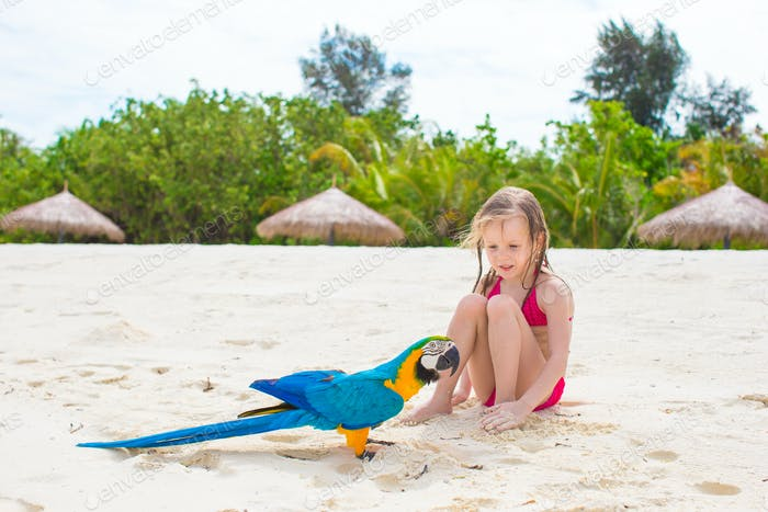 Adorable happy little girl with colorful parrot during beach vacation