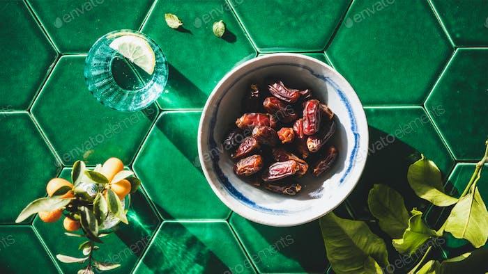 Flat-lay of Islamic Ramadan Iftar food over green tile table
