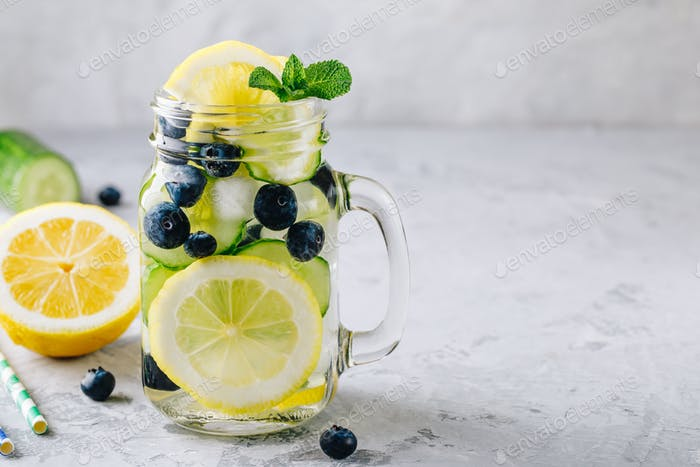 Infused detox water with lemon and cucumber slices, blueberry and mint.