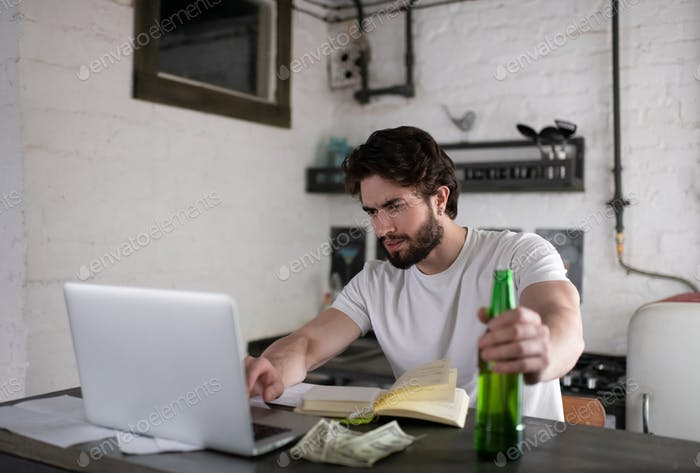 Stressed man using laptop to find job