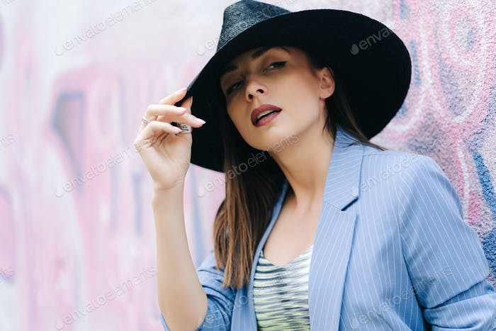 Fashion portrait of a young girl dressed in a blue striped jacket and black hat