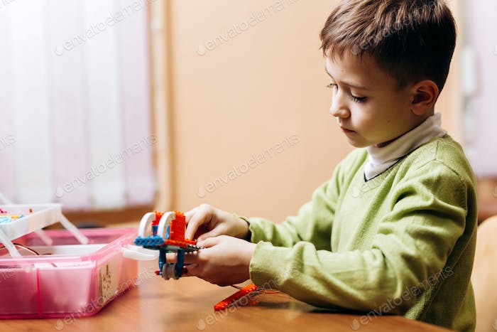 Boy dressed in green sweater sits at the table with opened box with details of robotic constructor
