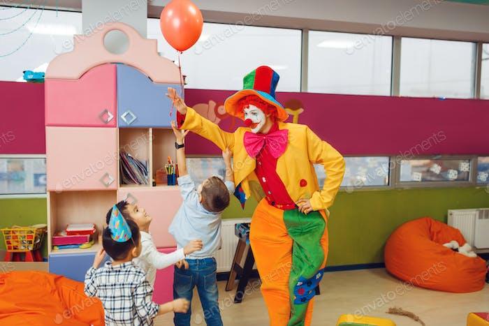 Lustiger Clown zeigt Tricks zu überraschen Kindern