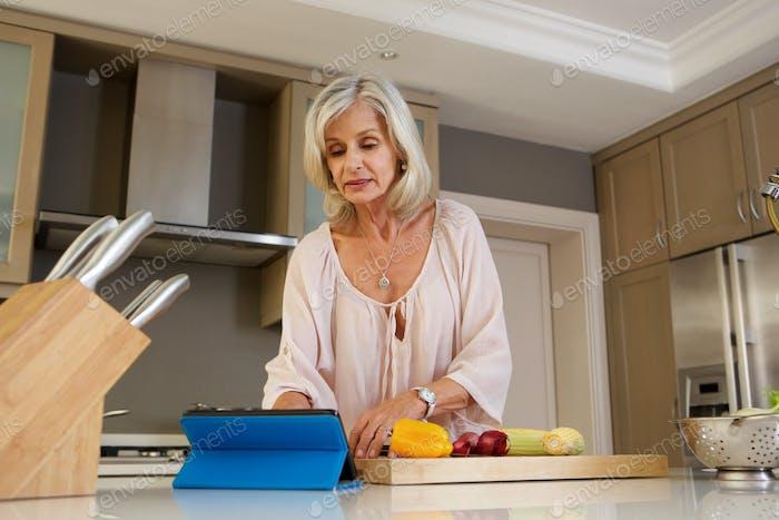 ältere Frau Lesen Rezept in der Küche auf Tablette