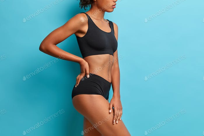 Profile shot of slim woman stands sideways wears black lingerie has perfect slim body isolated over