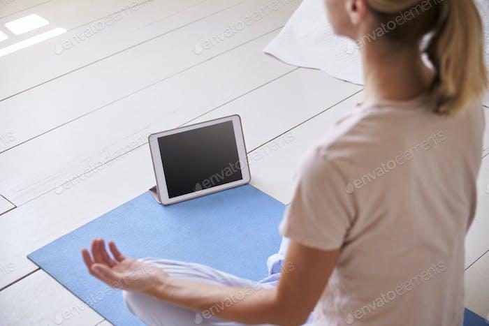 Woman With Digital Tablet Using Meditation App In Bedroom