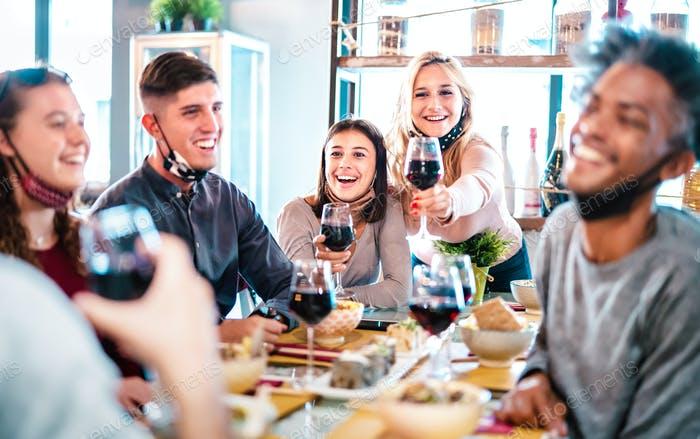 People toasting red wine at fashion restaurant bar with open face mask