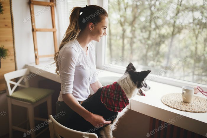 Beautiful woman happy while spending time with her dog at home