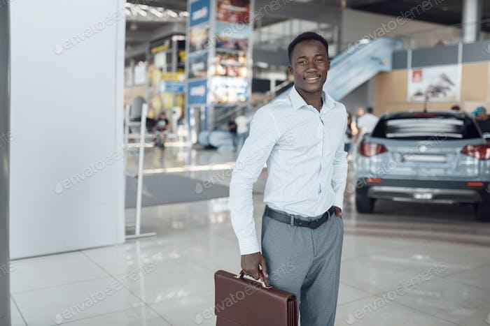 Lächelnder Geschäftsmann hält Aktentasche, Auto-Showroom