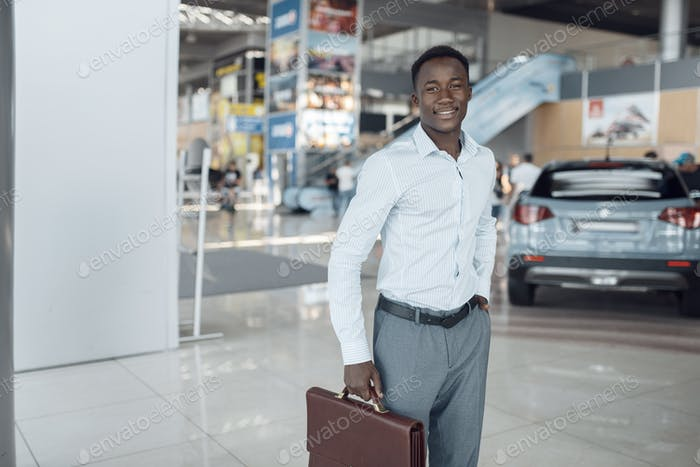 Smiling businessman holds briefcase, car showroom