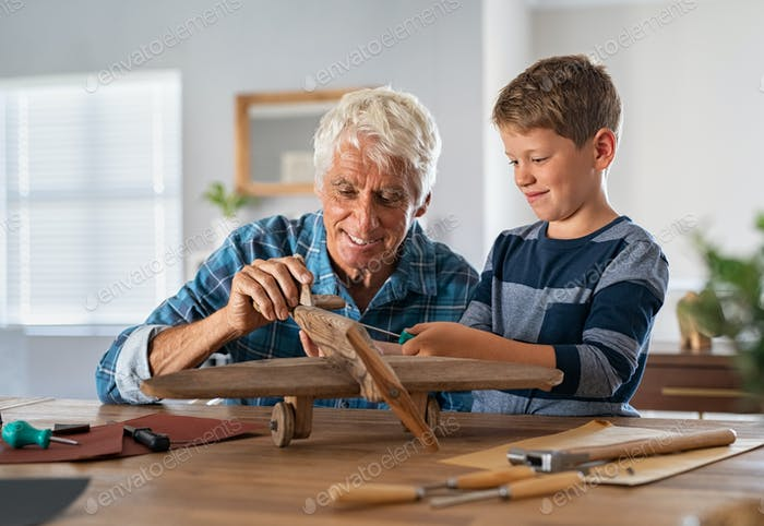 Old grandfather and child assembling wooden plane together