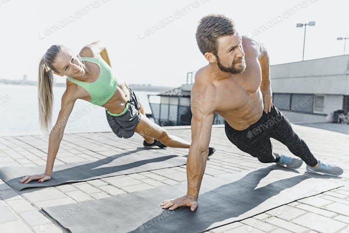 Fit Fitness Frau und Mann tun Fitness-Übungen im Freien in der Stadt