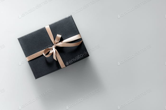 Gift wrapped in dark paper on pastel background