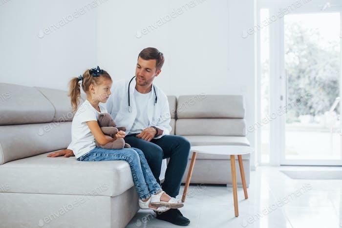 Männlicher Arzt in weißer Uniform sitzt in der Klinik mit kleinen Mädchen