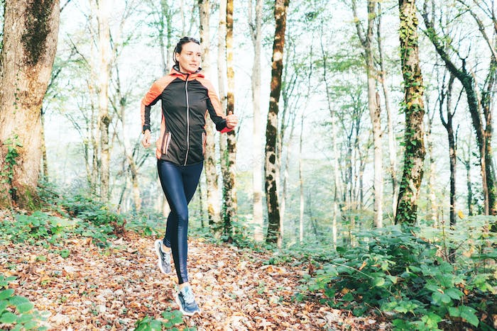 Young caucasian woman runner on a forest trail. Exercise in the fresh air. Healthy lifestyle.