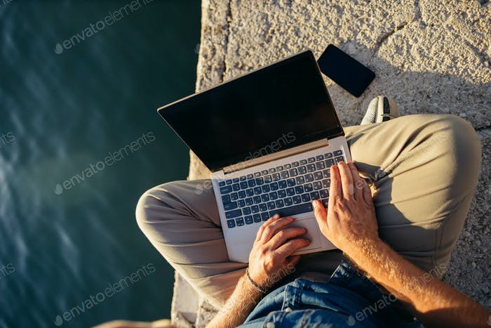 freelancer using laptop network on beach